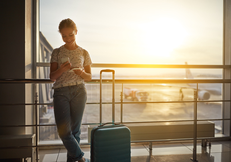 young woman waiting for  flying  at airport  at window  with a suitcase Reklamní fotografie - 93868220
