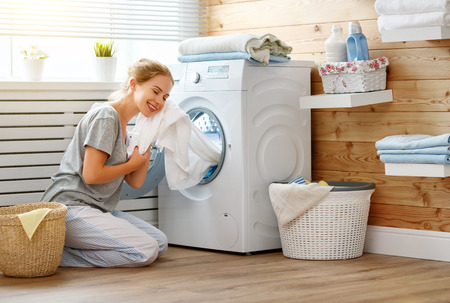 a Happy housewife woman in laundry room with washing machine Stok Fotoğraf - 93868234
