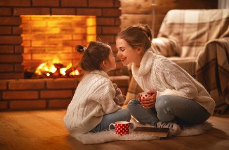 mère de famille et enfant fille de boire du thé et de rire sur la soirée d & # 39 ; hiver par cheminée