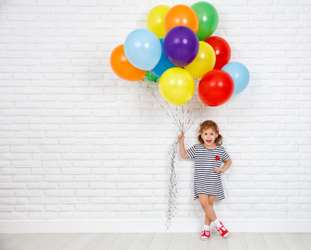 Happy funny child girl with a colorful balloons near an empty white brick wall