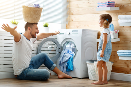 Happy family man father  householder and child daughter in laundry with washing machine  스톡 콘텐츠