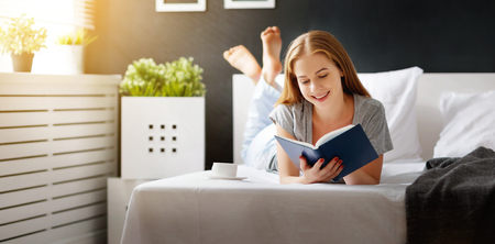 Happy young woman reads book and drinks coffee in bed in   morning