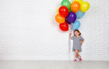 Gelukkig grappig kindmeisje met kleurrijke ballons dichtbij een lege witte bakstenen muur