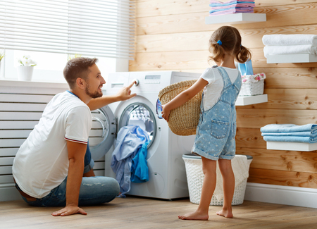 Happy family man father  householder and child daughter in laundry with washing machine  Banque d'images