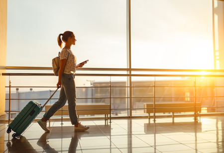 young woman goes  at airport  at window  with a suitcase waiting for  plane Reklamní fotografie - 93868289