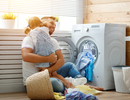 Happy family man father  householder and child daughter in laundry with washing machine Banco de Imagens - 93868381