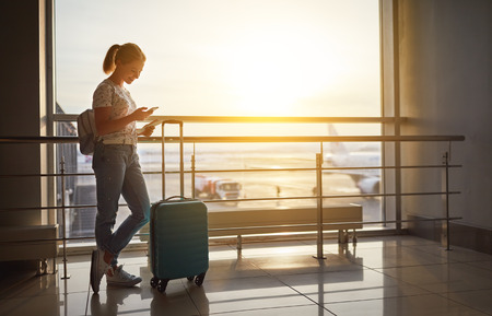 young woman waiting for  flying  at airport  at window  with a suitcase Reklamní fotografie - 93868383