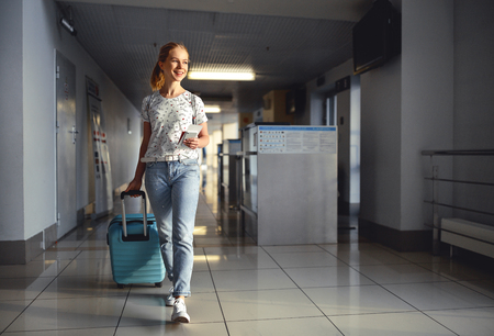 young woman goes  at airport  at window  with a suitcase waiting for  plane  Reklamní fotografie