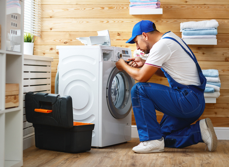 working man plumber repairs a washing machine in   laundry Imagens - 93868394