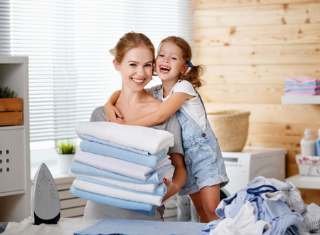 Happy family mother housewife and child daughter  ironing clothes iron in laundry at home Standard-Bild