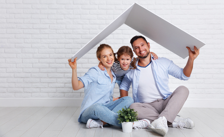 若い家族を収容する概念。空のレンガの壁に屋根を持つ新しい家の母父と子供