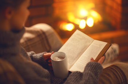 book and cup of coffee in hands of girl on winter autumn evening near fireplace
