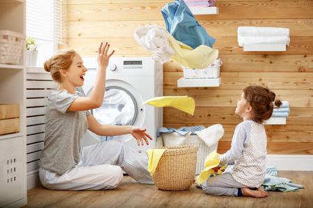mère heureuse mère mère et fille enfant dans le linge avec machine à laver