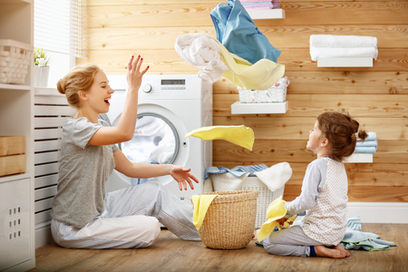 Happy family mother housewife and child daughter in laundry with washing machine  Banque d'images