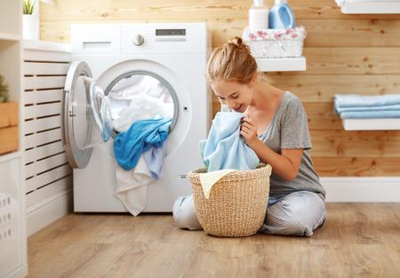 una donna casalinga felice in lavanderia con lavatrice