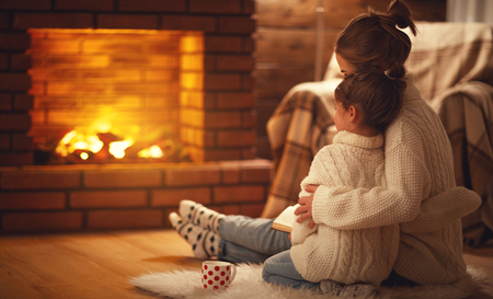 family mother and child daughter hugs and warm on winter evening by fireplace Stock Photo