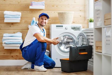 working man plumber repairs a washing machine in   laundry Archivio Fotografico