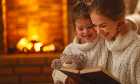 幸せな家族の母と子供の娘は冬の秋の夜に本を読みます