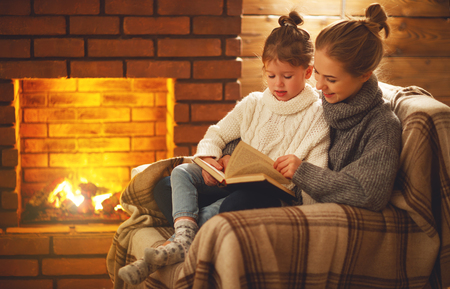 happy family mother and child daughter read a book on winter autumn evening near fireplace Archivio Fotografico