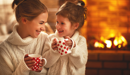 family mother and child daughter drinking tea and laughing on winter evening by fireplace