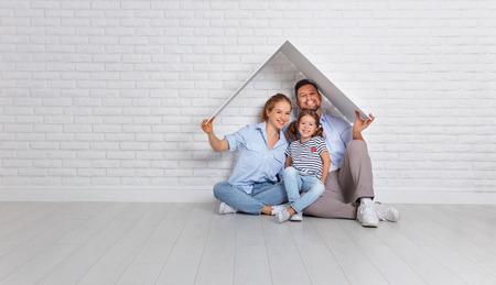 Concept voor een jong gezin. Moedervader en kind in nieuw huis met een dak bij lege bakstenen muur Stockfoto - 93931143