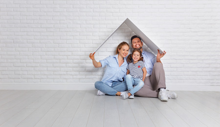concept housing a young family. Mother father and child in new house with a roof at empty brick wall Archivio Fotografico