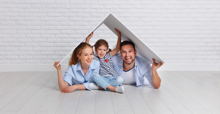 concept housing a young family. Mother father and child in new house with a roof at empty brick wall Banque d'images