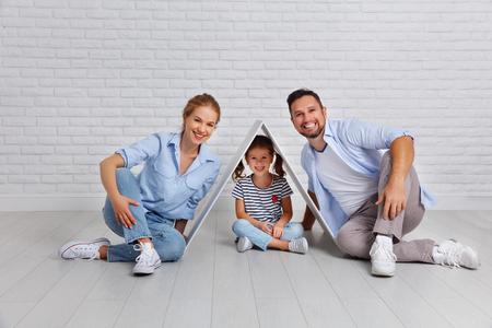 concept voor een jong gezin. Moedervader en kind in nieuw huis met een dak bij lege bakstenen muur Stockfoto