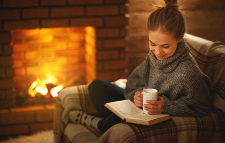 young woman enjoys reading a book by the fireplace on a winter evening Banco de Imagens - 94299774