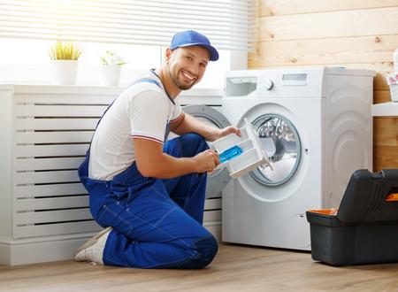 働く男性配管工は洗濯物の洗濯機を修理する