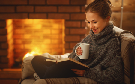 young woman enjoys reading a book by the fireplace on a winter evening