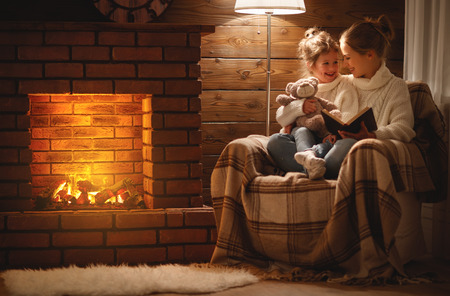 happy family mother and child daughter read a book on winter autumn evening near fireplace Stockfoto
