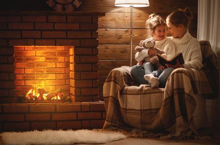 szczęśliwa rodzina matka i córka dziecko czytają książkę w zimowy jesienny wieczór przy kominku
