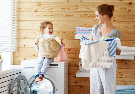 Happy family mother housewife and child daughter in laundry with washing machine Stok Fotoğraf - 93867462