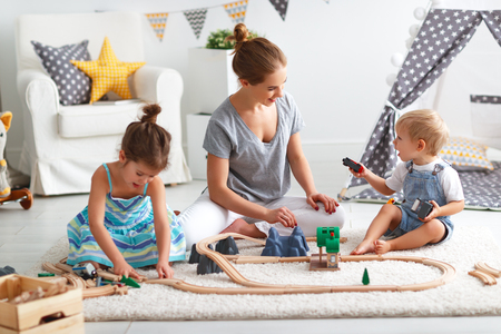 family mother and children play a toy railway in the playroom  Stok Fotoğraf