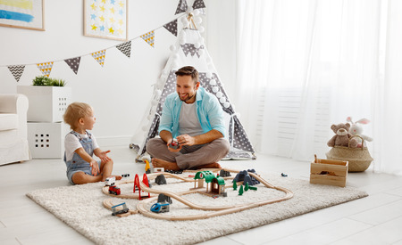 happy family father and child son playing together in toy railway in playroom  Reklamní fotografie