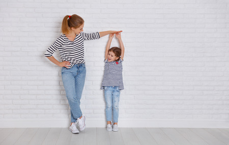 concept of the family. mother measures growth of child to a daughter near an empty wall