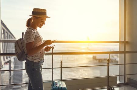 スーツケースを持って窓際で空港で飛行を待っている若い女性