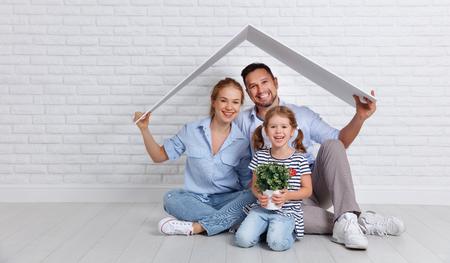 koncepcja mieszkania młodej rodziny. Matka, ojciec i dziecko w nowym domu z dachem przy pustym murem