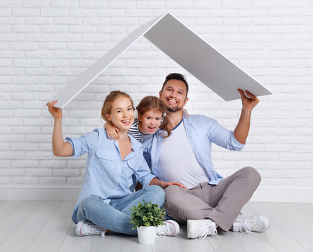 concept housing a young family. Mother father and child in new house with a roof at empty brick wall Stockfoto