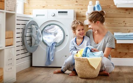 洗濯機で洗濯で幸せな家族の主婦と子供の娘
