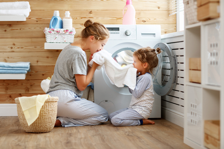Happy family mother housewife and child daughter in laundry with washing machine  Archivio Fotografico