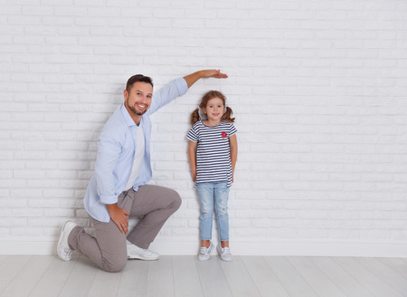 concept of the family. the father measures growth of child to a daughter near an empty wall Banco de Imagens - 94520460