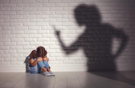 Violencia doméstica. madre enojada regaña a hija asustada sentada en el piso
