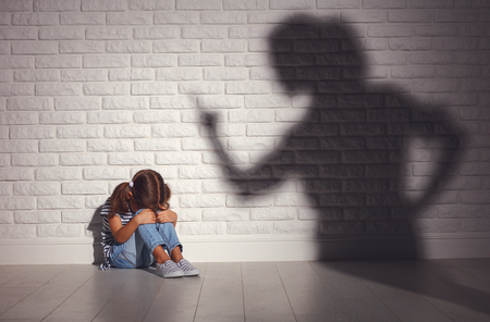 domestic violence. angry mother scolds   frightened daughter sitting on floor