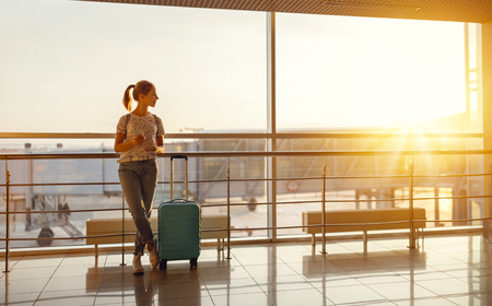 young woman waiting for  flying  at airport  at window  with a suitcase Reklamní fotografie - 94882200