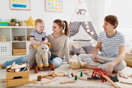 family mother father and baby son playing together in childrens playroom  Stock Photo
