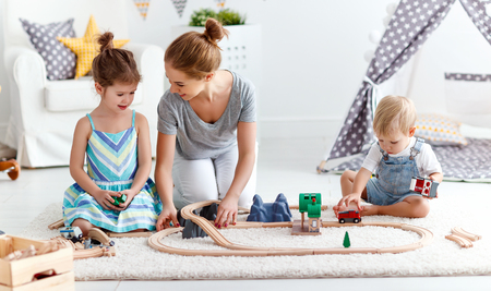 family mother and children play a toy railway in the playroom  Stock Photo