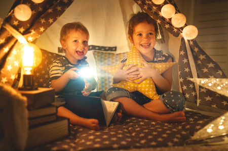 children boy and girl reading book with flashlight in  tent at night  Banco de Imagens