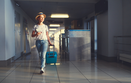 young woman goes  at airport  at window  with a suitcase waiting for  plane Reklamní fotografie - 94882330